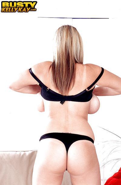 Blonde European MILF pornstar Kelly Kay unleashing huge boobs from lingerie