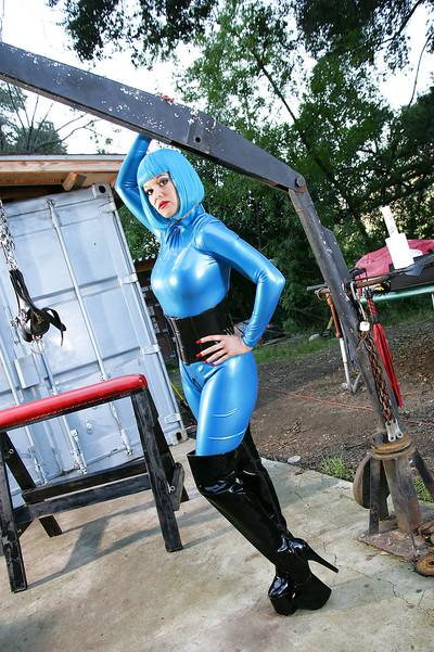 Kinky babe in latex clothes and black boots posing outdoor