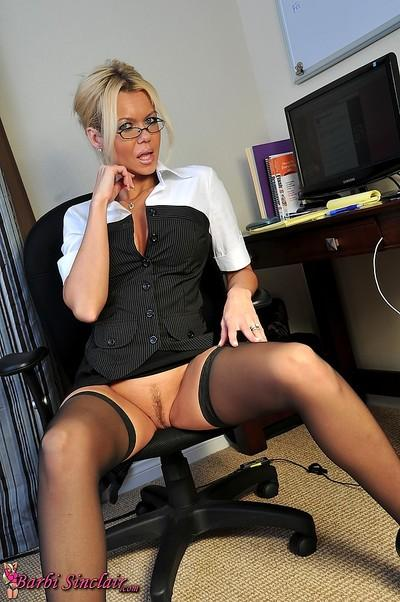 Classy MILF secretary shows off her wonderful body wearing black stockings in her office.