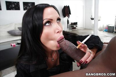 Buxom brunette MILF Nikki Benz giving a huge black cock a tit fucking