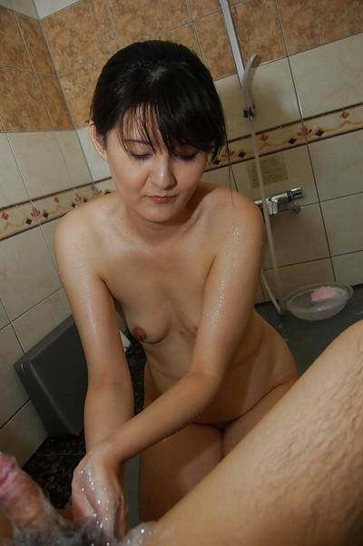 Sassy asian MILF gives a soapy handjob and blows a stiff cock in the bathroom