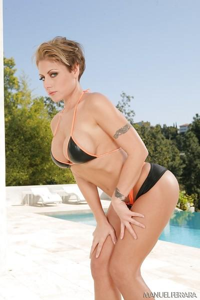 Short haired blonde MILF Velicity Von posing topless beside swimming pool