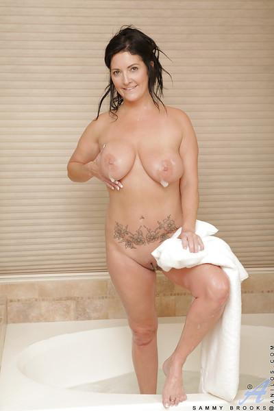 Well-stacked brunette MILF taking bath and teasing her hungry slit