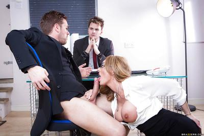 Chesty blonde MILF Stacey Saran giving boss blowjob in front of co-workers