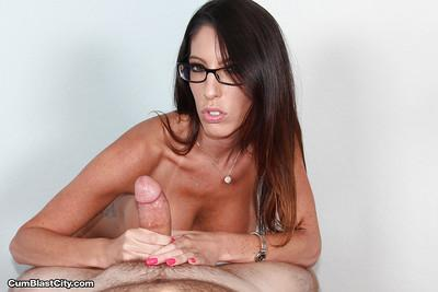 Busty glasses adorned brunette MILF pornstar jerking off cock