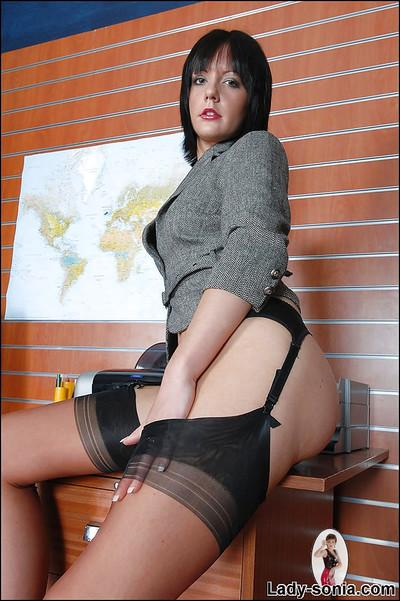 Sassy raven-haired MILF posing with no skirt at her work place