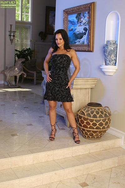 Tall brunette MILF Lisa Ann letting large boobs loose from dress