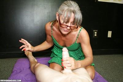Mature lady in glasses smoking and giving a sensual handjob