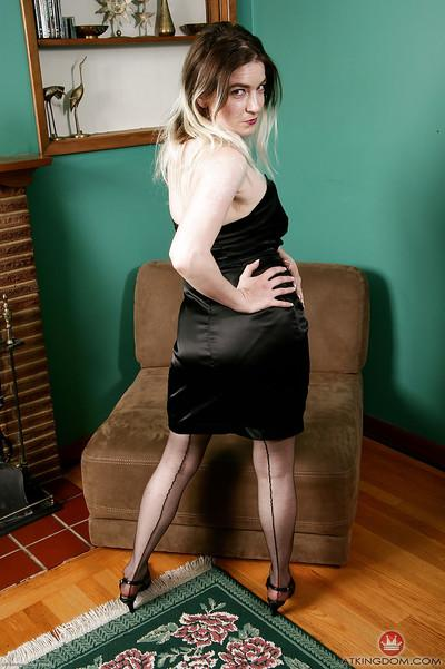 Experienced solo model Tink striking sexy poses in black dress and hose