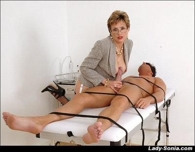 Voluptuous mature femdom gives a handjob to a bound and blindfolded guy
