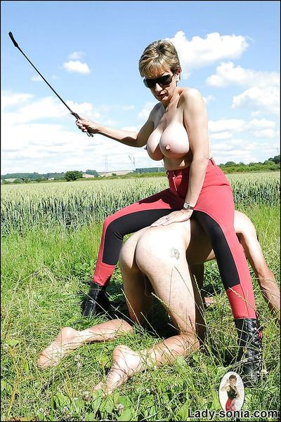 Busty femdom in sunglasses treats her manslave like a horse