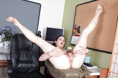 Mature office worker Sunshine taking time out to rub hairy vagina