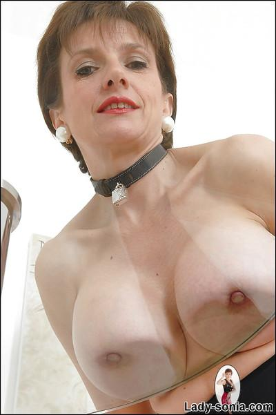 Juggy mature fetish lady in provocative outfit exposing her jugs and fanny