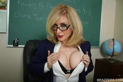 Lusty teacher Nina Hartley exposing her round titties in the classroom