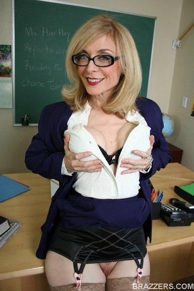 Lusty teacher Nina Hartley exposing her round titties in the classroom