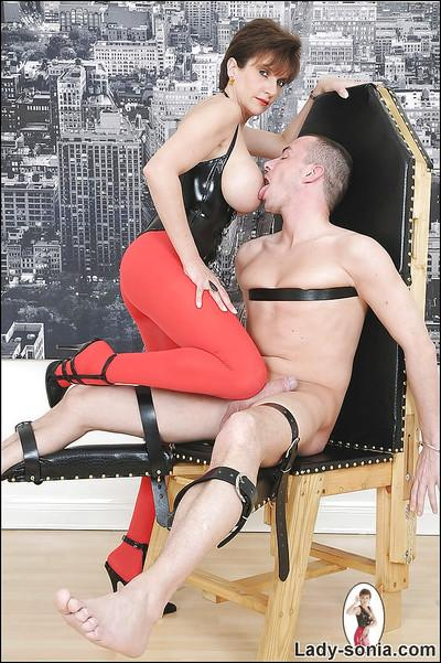 Big busted mature femdom in red pantyhose playing with her male pet