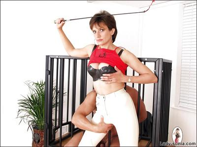 Fully clothed mature femdom spends some good time with her caged pet