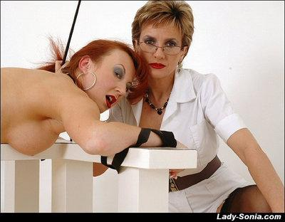 Seductive mature lady in glasses spanking her friend