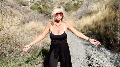 Mature blonde Sandra Otterson is walking topless outdoors so sexy