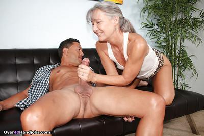 Grey haired cougar jerks off a younger man