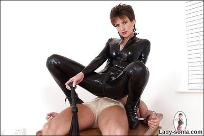 Saucy fetish lady in black latex suit has some fun with her bound male pet