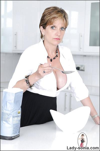 Busty mature lady on high heels stripping off her clothes in the kitchen