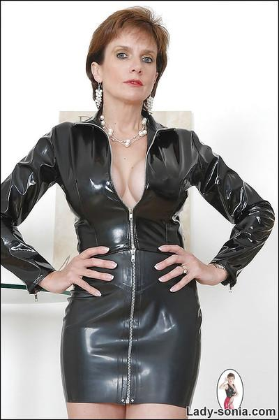 Sexy mature lady in latex dress doing upskirt and flashing her boobs