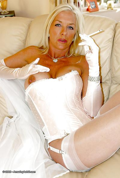 Older blonde dame in wedding dress and lingeri0s having a smoke