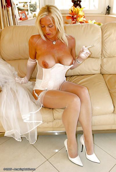 Older blonde dame in wedding dress and lingeri0s having a smoke