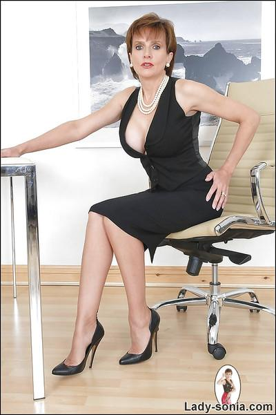 Shapely mature lady in glasses posing in a low neckline dress