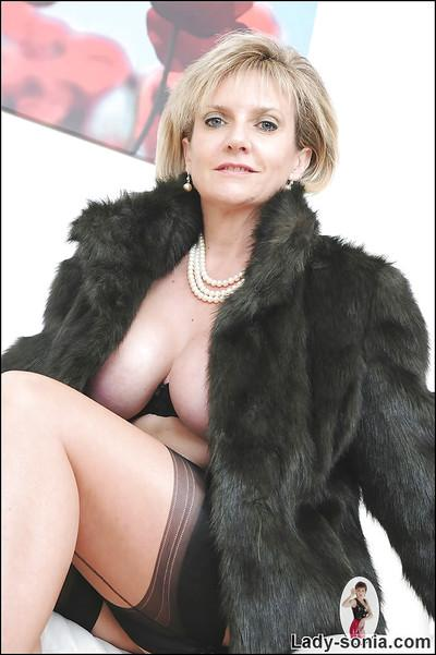 Mature blonde with big tits Lady Sonia in a fetish scene while wearing stockings