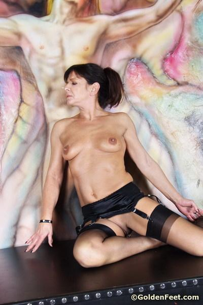 Saucy mature British broad Lady Sarah on cross in nylons and garters