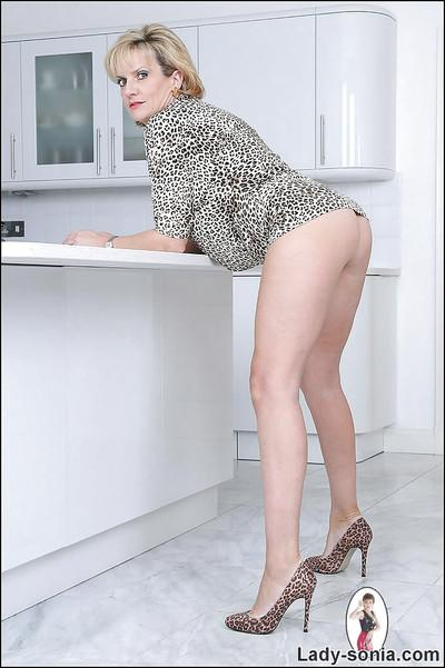 Seductive mature lady showing off her tits and pussy in the kitchen