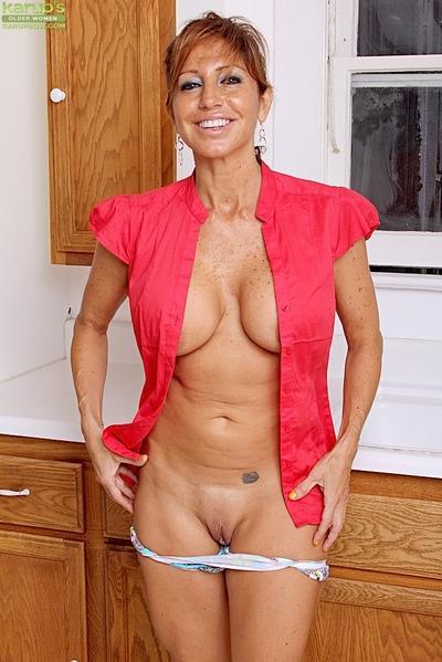 Buxom older woman Tara Holiday flaunting big natural breasts in kitchen