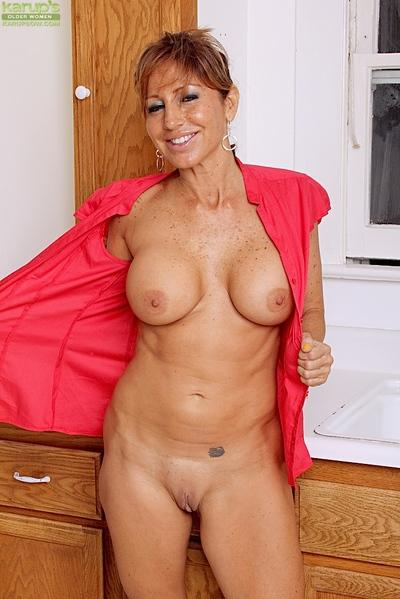 Buxom older woman Tara Holiday flaunting big natural breasts in kitchen