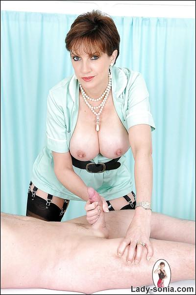 Busty mature femdom in stockings jerks a hard cock until it blasts with cum