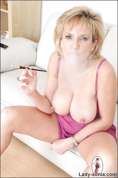 Lusty fetish lady in lingerie smoking and revealing her big boobs