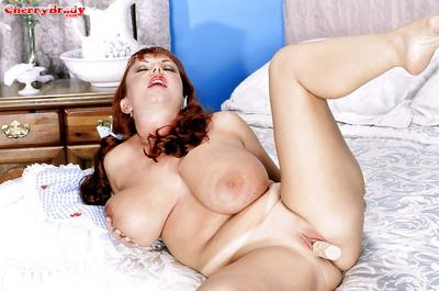 Older redhead Cherry Brady flaunting huge boobs in stockings and garters