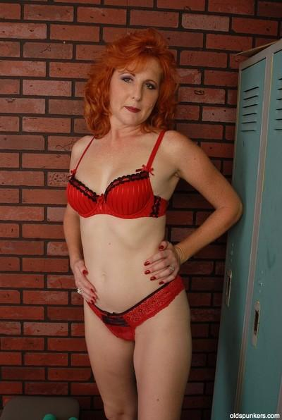 Redhead mature Sasha demonstrates her boobies in the dressing room