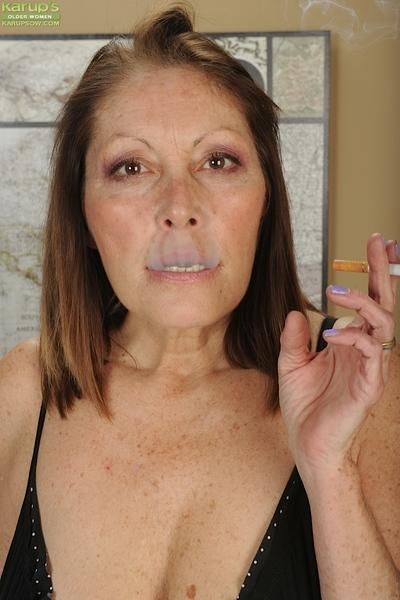 Older broad Jane McWilliams enjoying a smoke while fondling big boobs