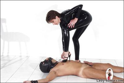 Mature femdom in latex outfit torturing her masked male pet