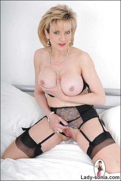 Mature fetish lady in lingerie and stockings revealing her jugs and pussy