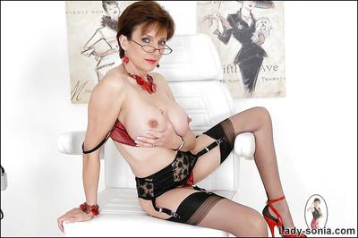 Full-bosomed mature fetish lady in glasses posing in erotic lingerie