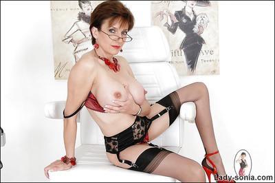 Full-bosomed mature fetish lady in glasses posing in erotic lingerie