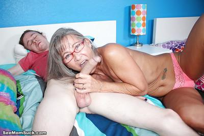 Glasses adorned granny sucks and tugs on a younger man