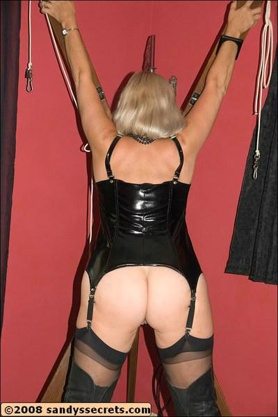 Sandy Spain wearing latex corset and stockings while playing with a strapon
