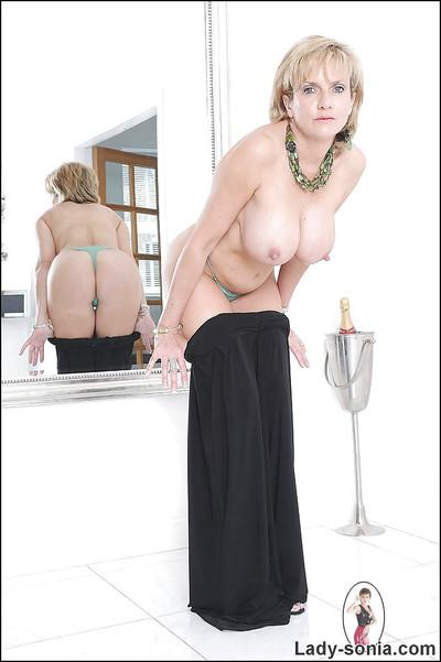 Seductive mature lady with huge tits stripping in front of the mirror