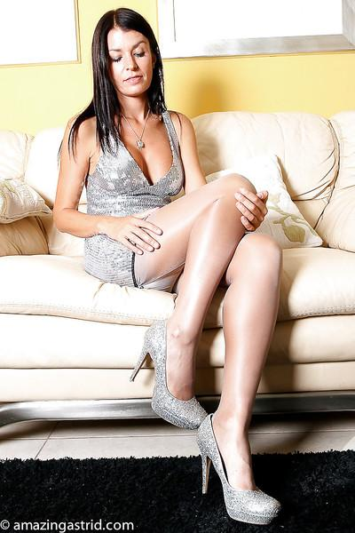 Brunette lady from Europe kicks off pumps to display nylon encased feet