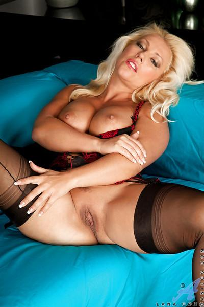 Steamy mature blonde in stockings revealing her big tits and shaved gash