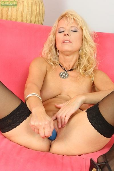 Mature lassie in stockings pleasing her wet cunt with a vibrator